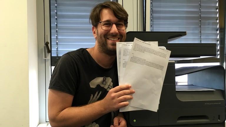 Sebastian Sonntag hält drei Faxe in der Hand