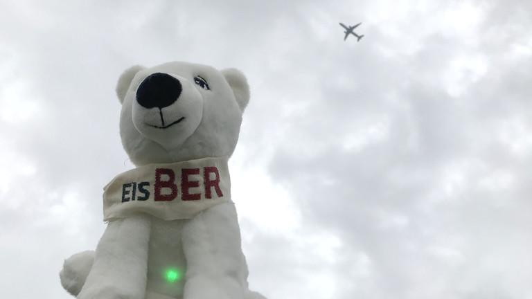 """Netzbasteln #151: Ein Stofftier-Eisbär mit Aufschrift """"EisBER"""" vor bewöltem Himmel, im Hintergrund fliegt ein Flugzeug vorbei"""
