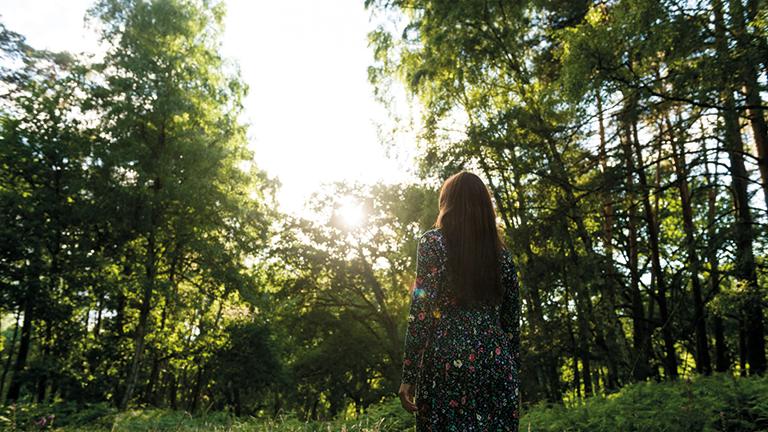Franziska Jebens im Wald mit dem Rücken zur Kamera