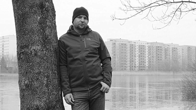 Porträt von Sebastian Caspar, im Hintergrund eine Plattenbau-Siedlung.