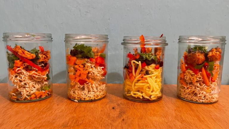 In Schraubgläser werden Mie-Nudeln, Paprika, Möhre, Koriander, Sezuan-Tofu und Frühlingszwiebeln geschichtet.