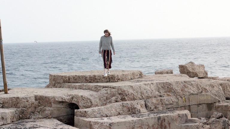 Eine Frau auf Klippen vor dem Meer.