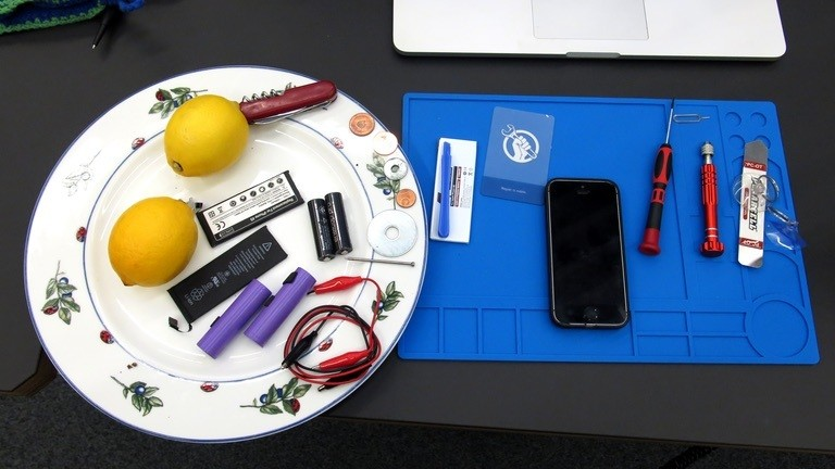 Ein Smartphone und diverse Werkzeuge liegen auf einem Tisch.