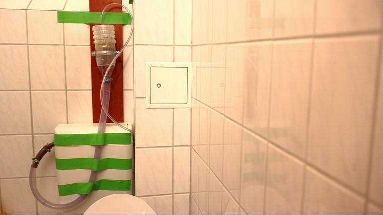 Die fertige Konstruktion zu Hause im Badezimmer. Das Wasser fließt über den kleinen Schlauch in den Sprossenturm - und über das improvisierte Siphon des großen Schlauchs zurück in den Spülkasten.