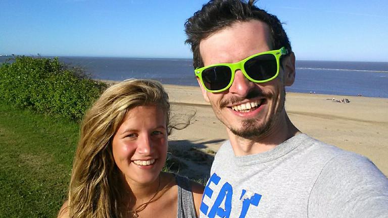 Lachender Mann mit einer Frau an einem Strand.