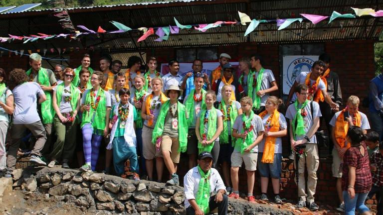 Jugendliche mit bunten Umhängen und Blumenketten