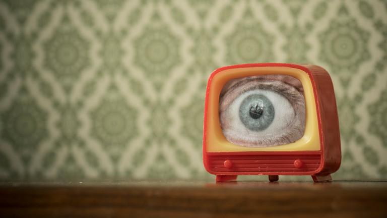 Ein Spielzeug-Fernseher aus dem ein Auge in Großaufnahme herausschaut.