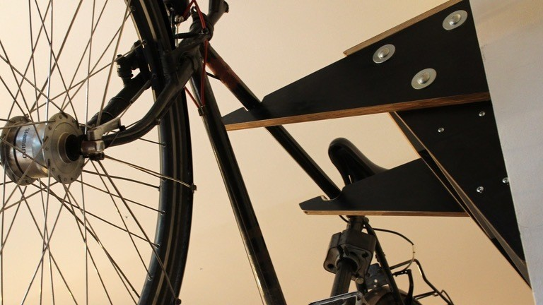 Ein Herrenrad hängt an eine Wandhalter für Fahrräder, der an der Wand verschraubt ist.