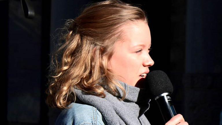 Carla Reemtsma, Jugendbotschafterin der Entwicklungsorganisation ONE, auf einer Bühne vor Publikum mit einem Mikro in der Hand.