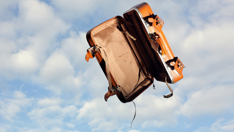 leerer fliegender Koffer vor Himmel