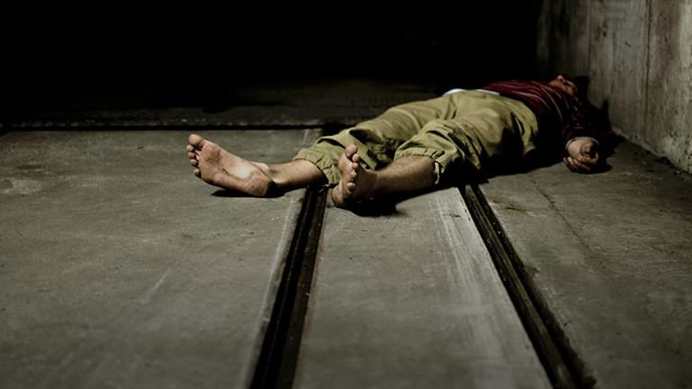Ein Mensch liegt auf einem Betonboden