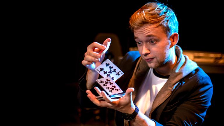 Der Zauberer Marc Weide führt einen Kartentrick vor.