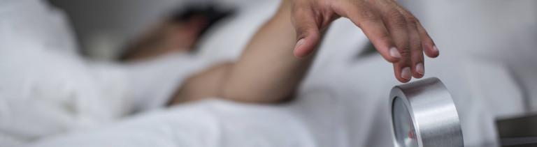 Ein Mann liegt im Bett und greift herüber zu seinem Wecker, um den Alarm auszuschalten.
