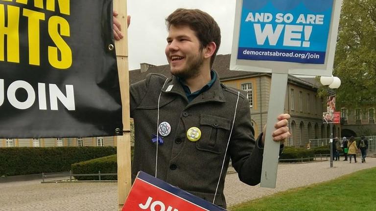 John Grosser hält Wahlplakate hoch