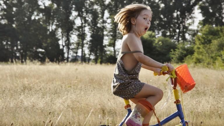 Ein Kind auf dem Fahrrad, guckt lustig in die Kamera.