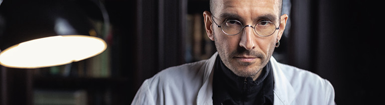 Kriminalbiologe Mark Benecke sitzt im weißen Kittel am Schreibtisch.