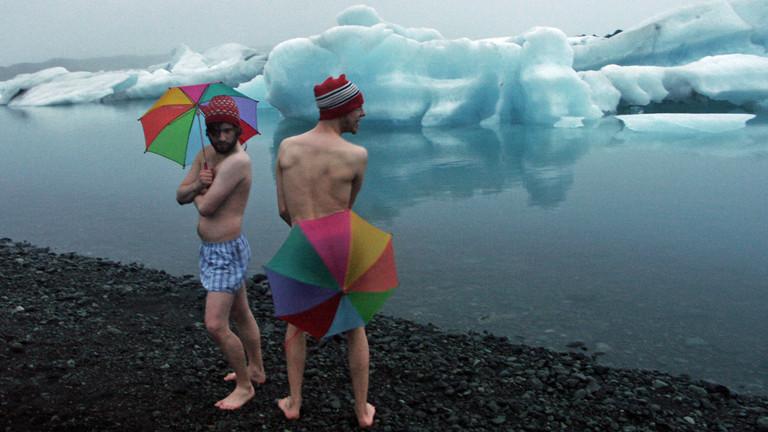 Zwei Maenner in Unterhosen vor Eisbergen