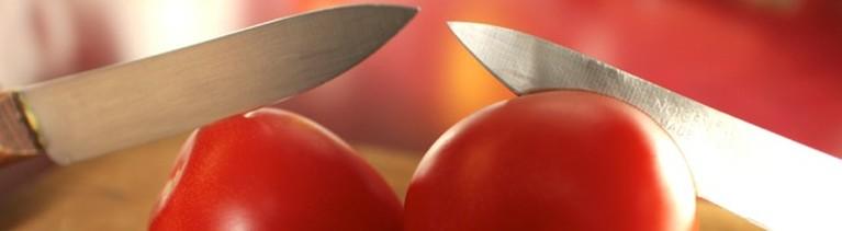 Zwei Messer stecken in zwei Tomaten.