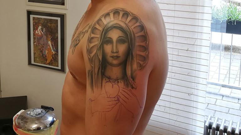 Tätowiertes Marienbild auf dem Oberarm eines Mannes