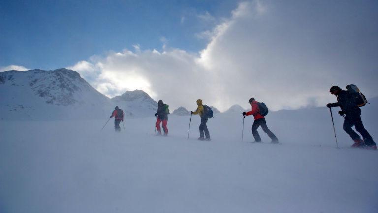 Eine Gruppe Skifahrer steigt bei heftigem Wind und Schneetreiben auf dem Pitztaler Gletscher auf.