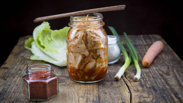 Ein Glas Kimchi, Kohl, Frühlingszwiebeln und eine Karotte auf einem Holztisch.