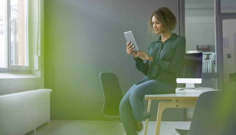Frau, die auf einem Schreibtisch sitzt und ein Tablet in der Hand hält.