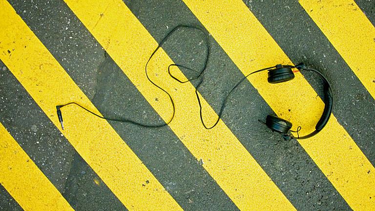 Kopfhörer auf schwarz-gelbem Asphalt