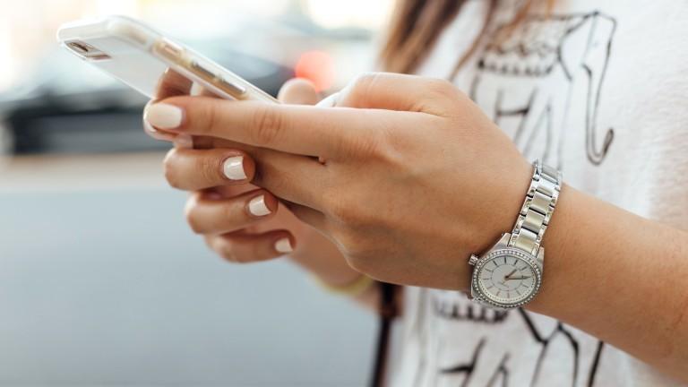 Eine Frau mit weiß lackierten Fingernägeln und Armbanduhr, hält eine Smartphone in beiden Händen.