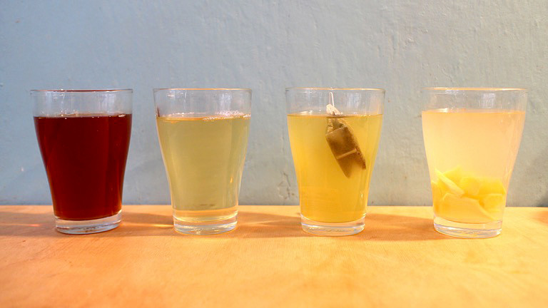 Vier Gläser mit unterschiedlichem Tee.