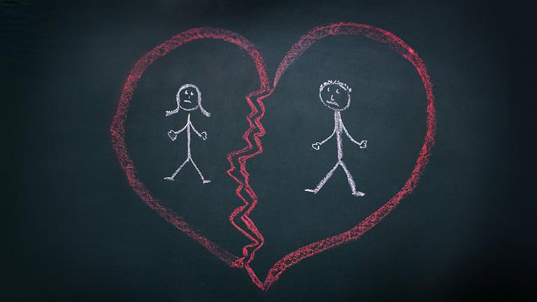 Ein zerbrochenes Herz mit zwei Menschen darin ist mit Kreide auf eine schwarze Tafel gemalt.