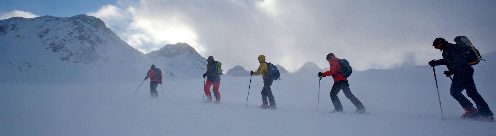 Eine Gruppe Skifahrer steigt bei heftigem Wind und Schneetreiben auf dem Pitztaler Gletscher auf