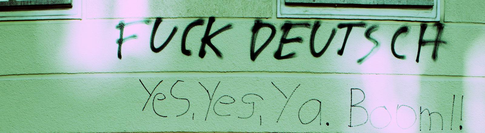 """An einer Hauswand steht als Graffiti aufgesprüht: """"Fuck Deutsch""""."""