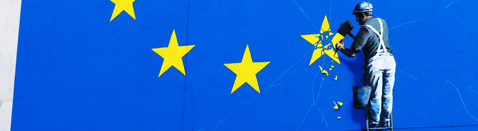 Streetart: Mann demoliert einen Stern der Europaflagge.