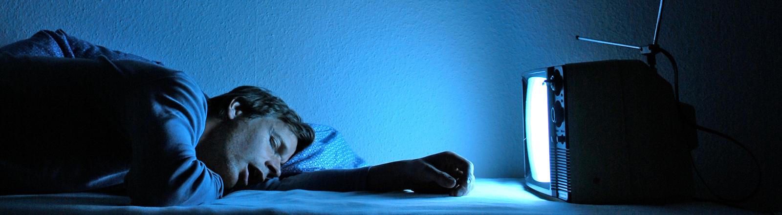 Ein Mann schläft vorm Fernseher.