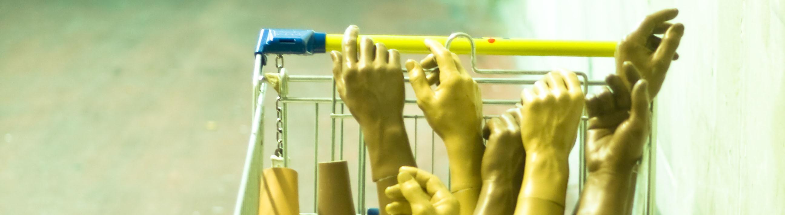 Hände und Unterarme von Schaufensterpuppen in einem Einkaufswagen
