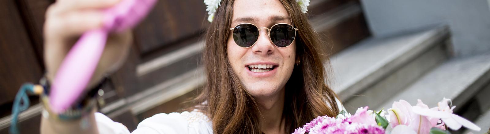 Mann mit Blumen im Haar.