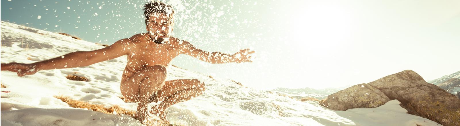 Nackter Mann springt im Sand herum