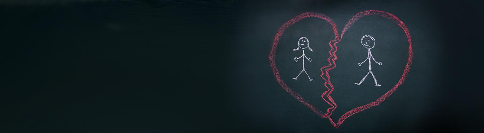 Ein zerbrochenes Herz mit zwei Strichmännchen darin ist mit Kreide auf eine schwarze Tafel gemalt.