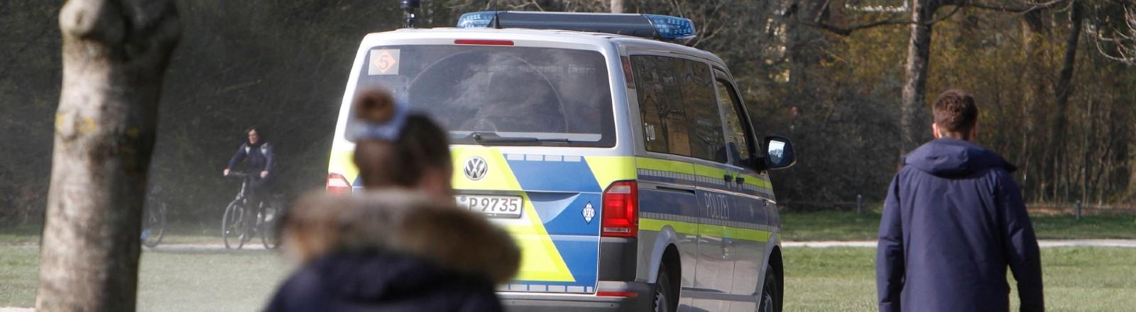 Eine Polizeistreife der Landespolizei Bayern kontrolliert anlässlich der Coronakrise die Einhaltung der Kontaktverbote sowie Mindestabstände in dem von Passanten und Ausflüglern stark frequentierten Park Englischer Garten in München.