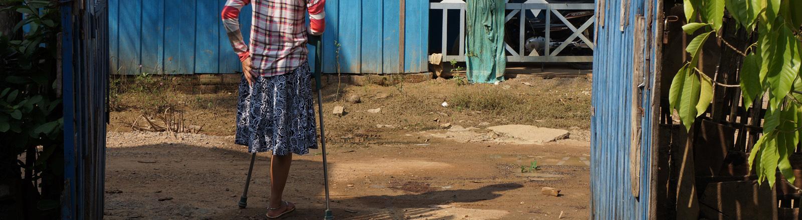 Eine Frau mit einer Beinprothese steht vor einem Haus.