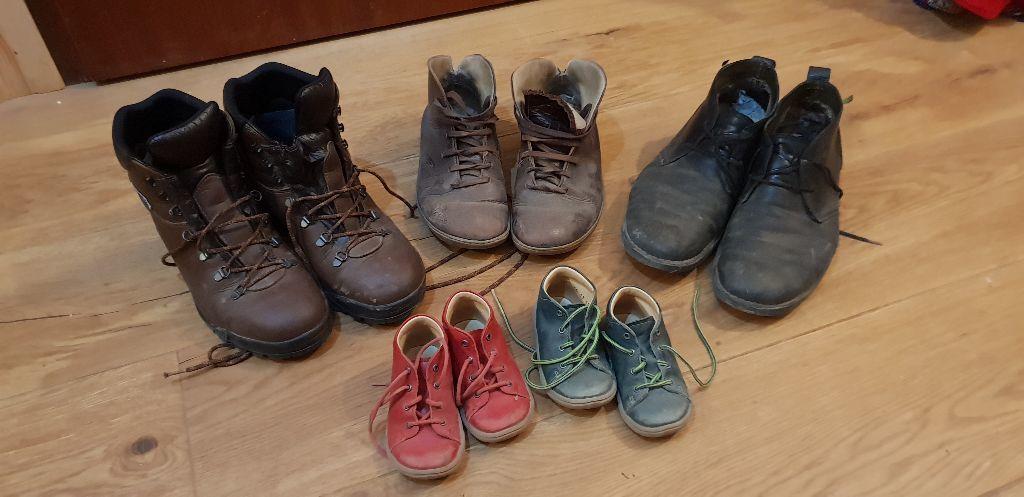 Drei Schuhe von erwachsenen Menschen und zwei von Kindern