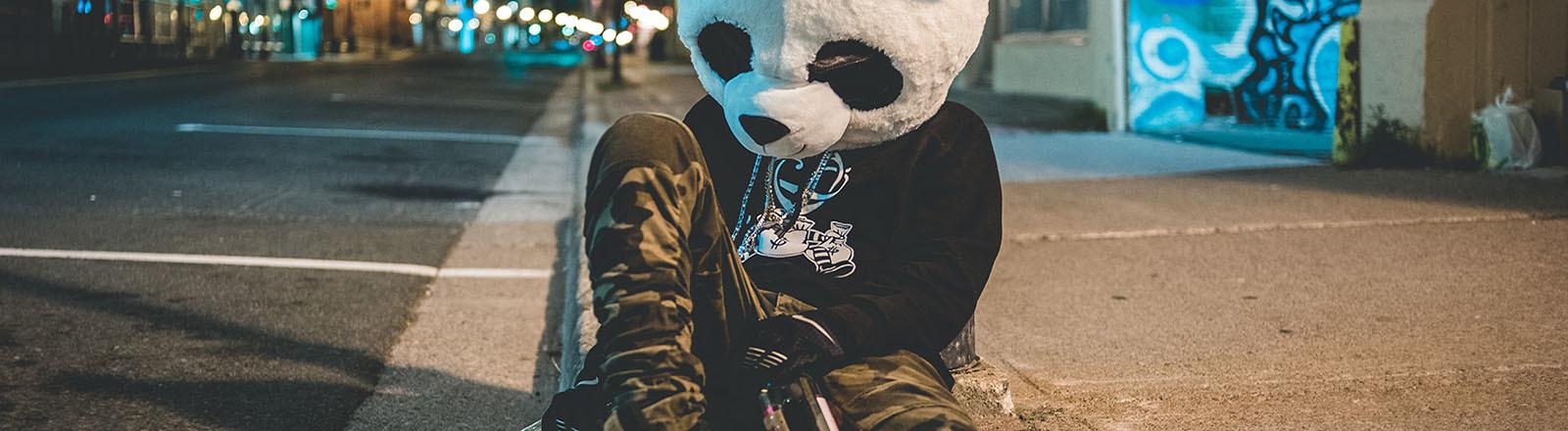 Mensch im Pandakostüm lehnt sich an eine Laterne