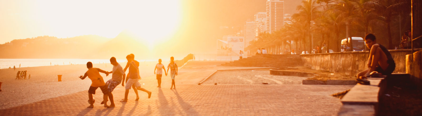 Kinder spielen in Brasilien im Sonnenuntergang Fußball.
