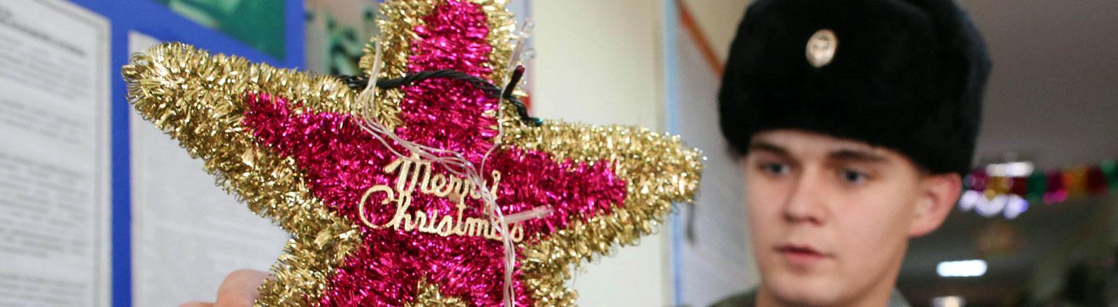 Ein russischer Mann dekoriert einen Weihnachtsbaum.