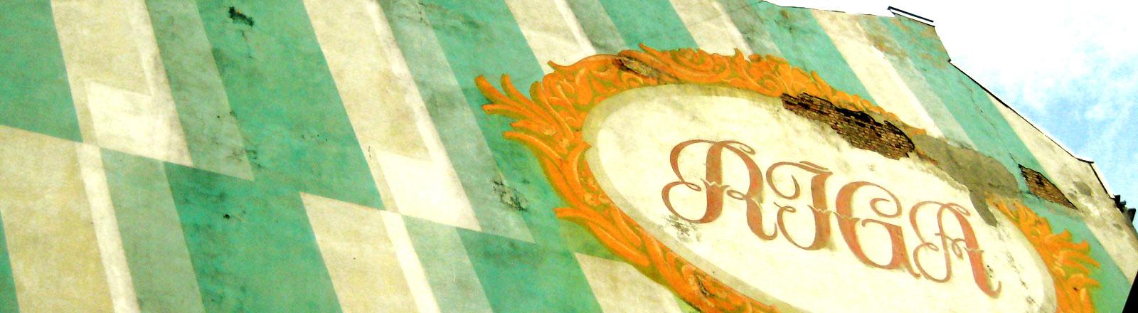 """An einer grün und grau gestreiften Wand steht das Wort """"Riga""""."""