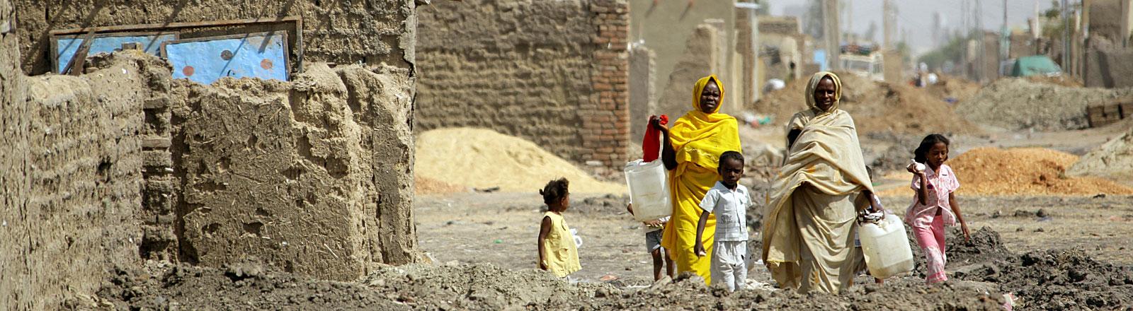 Durch Ruinen gehen sudanesische Frauen mit Kanistern zur einer Wasserstelle in der Stadt Kosti rund 300 Kilometer südlich von der Hauptstadt Khartum im Sudan.