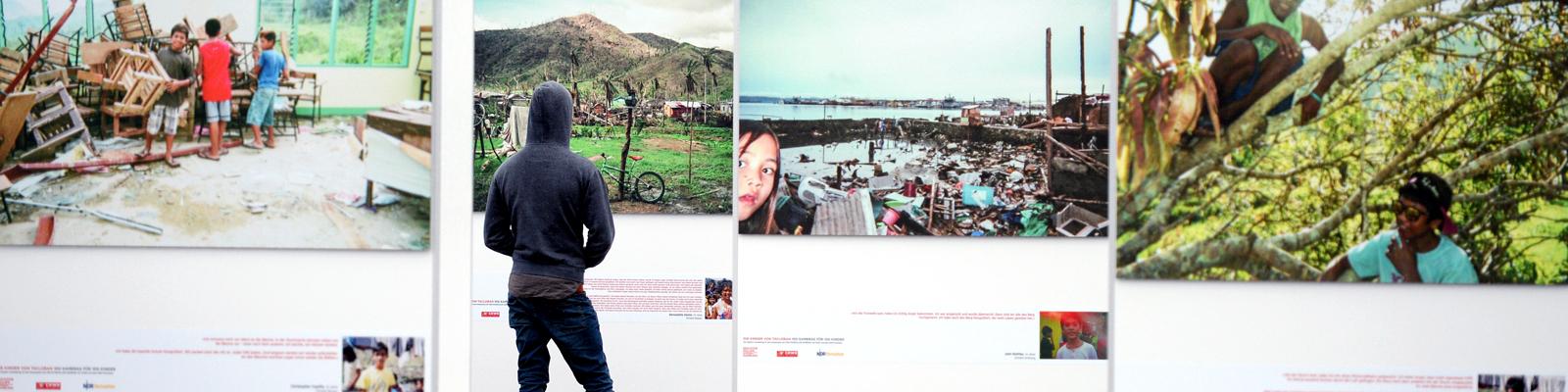 """Ein Besucher betrachtet die Bilder des Projekts von Philipp Abresch """"Die Kinder von Tacloban - 100 Kameras für 100 Kinder""""."""