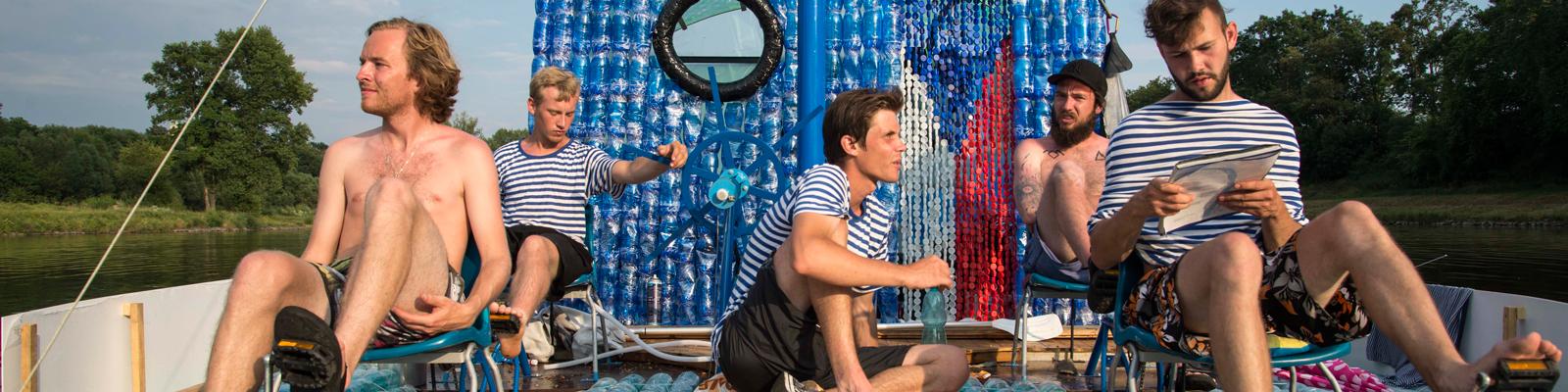 """Fünf junge Tschechen sitzen am 16.07.2014 auf ihrem Boot aus 4000 Plastikflaschen. Auf ihrem Boot """"Petburg"""" wollen sie auf der Elbe nach Hamburg fahren."""