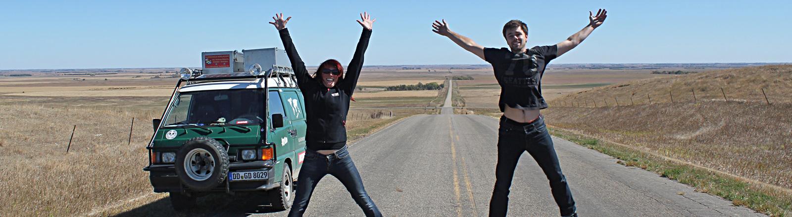 Kathi und Martin Zech stehen auf einer Straße und springen in die Luft. Hinter ihnen steht ihr grüner Kleinbus.