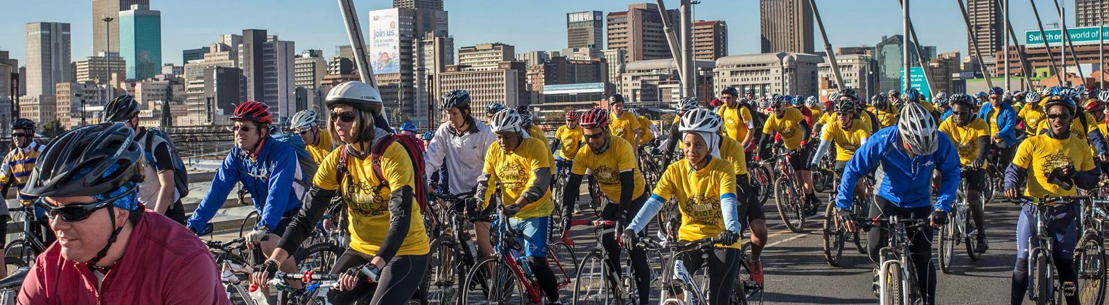 Über die Mandela-Brücke in Johannisburg fahren viele Fahrradfahrer. Sie tragen alle Helm und viele gelbe T-Shirts. Die Tour (Juli 2014) erinnert an Nelson Mandela und führt durch Johannisburg und Soweto; Bild: dpa
